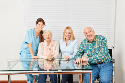 caregivers and elder couple smiling