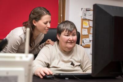 caregiver assisting woman using computer